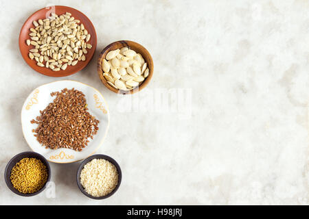 Assorted oil seeds (flax, sesame, pumpkin, sunflower, mustard) on stone background with copy space - organic ingredients - Stock Photo