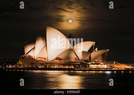 Sydney, Australia - 15 November 2016: Super full rusty moon rising over Sydney Opera House in Australia during unique - Stock Photo