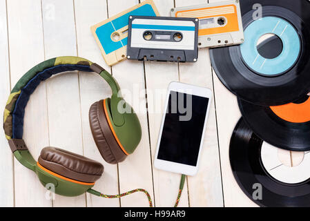 Music concept.Top view of gramophone records,audio cassettes,smart phone and headphones. - Stock Photo