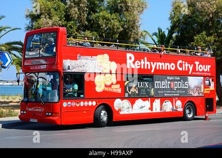 Tourists aboard a red open topped Rethymno City Tour bus, Rethymno, Crete, Greece, Europe. - Stock Photo