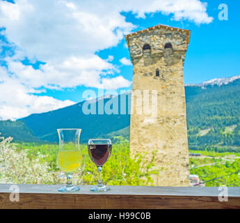 Two glasses of white and red wine on the terrace with the view on the medieval Svan tower and Mestia valley, Upper - Stock Photo