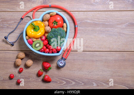 Heart shaped dish with vegetables and stethoscope isolated on wooden background and with copyspace on the right - Stock Photo