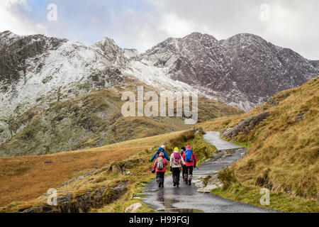 Hikers hiking on Miners' Track from Pen-y-Pass in Snowdon horseshoe with Y Lliwedd ahead and snow in winter. Snowdonia - Stock Photo
