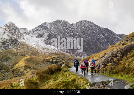 Hikers hiking on the Miners' Track in Snowdon horseshoe with Y Lliwedd ahead and snow in winter. Snowdonia National - Stock Photo