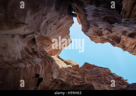 Towering red sandstone cliffs at Angola's coast line of the Namib Desert. - Stock Photo