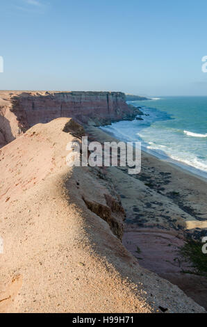Rough coast line with towering cliffs and wild ocean in Angola's Namib Desert. - Stock Photo