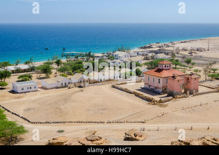 Small fishing village Mucuio with dominating Portuguese colonial building and white washed buildings in Angola. - Stock Photo