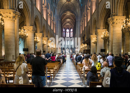 Unidentified tourists visiting the Notre Dame de Paris in Paris, France. The cathedral of Notre Dame is one of the - Stock Photo