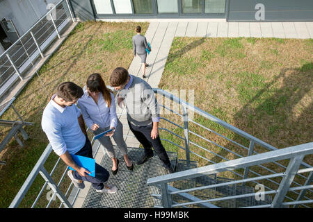 Group of business people talking on stairway - Stock Photo