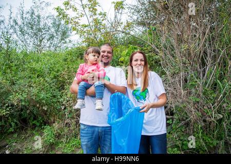 Teenage volunteers doing garbage cleanup in park - Stock Photo