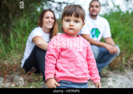 Toddler girl with parents in background - Stock Photo
