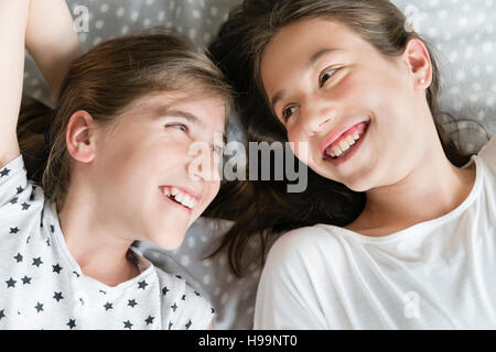 Two teenage girls relaxing in bedroom - Stock Photo