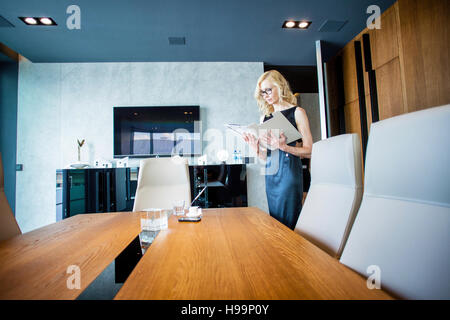 Businesswoman holding documents in board room - Stock Photo