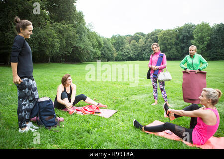 Young women relaxing after practicing yoga in park - Stock Photo