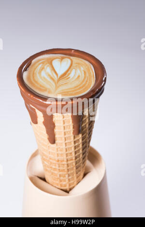 Coffee in waffle cone dipped in chocolate with drawings in cappuccino / latte milk foam, latte art, isolated - Stock Photo