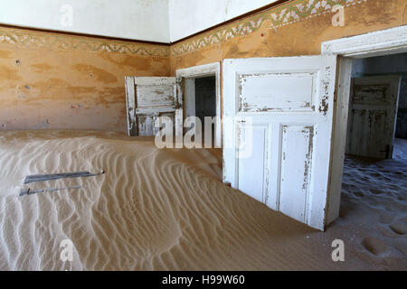 Rooms full of sand at the ghost town of Kolmanskop in Namibia - Stock Photo