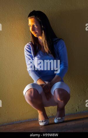 Pretty teen girl squat squatting in dark place corner near wall looking away aside watching sunset warm light facing - Stock Photo