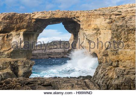 Waves crashing in to the Azure Window at Dweja on Gozo, Malta - Stock Photo