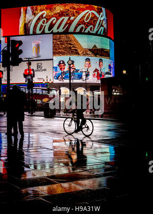 Rain reflects Piccadilly Circus lights in Central London - Stock Photo