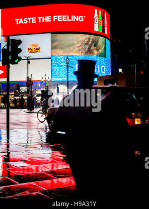 A man in a TopHat at Piccadilly Circus lights in Central London - Stock Photo