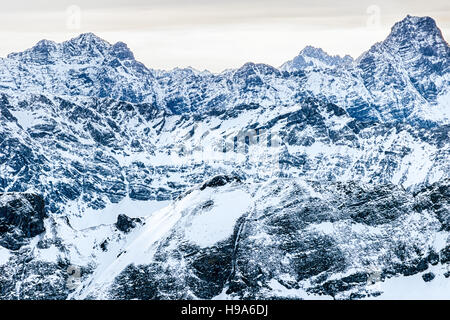Rocky steep snow-covered mountain downhills - Stock Photo