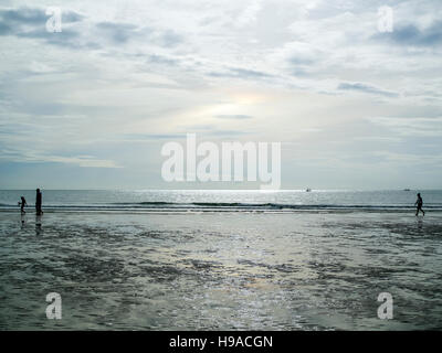 People walking on the beach in Hua Hin, Thailand. - Stock Photo