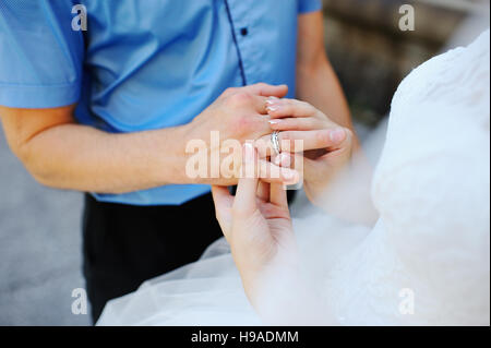 The groom wearing wedding ring for his bride hand Stock Photo