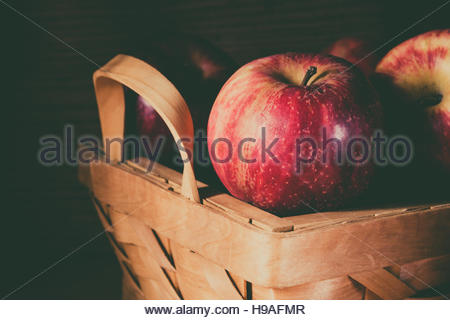 Red apples in basket on dark background - Stock Photo