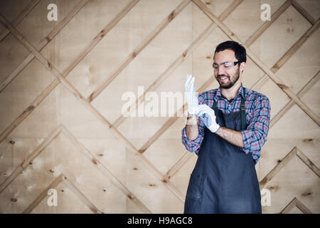 Portrait of a carpenter working in workshop wearing gloves - Stock Photo