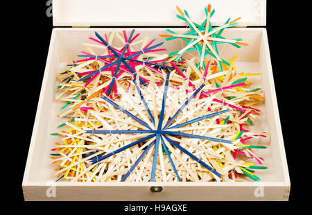 Straw stars Christmas decoration in wooden box. Handmade colorful decor for windows, as gifts or to hang on the - Stock Photo