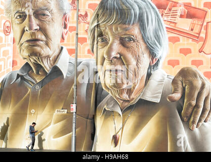 A pedestrian on a mobile phone passes a large mural on a wall in Lonsdale Street, Melbourne, Victoria, Australia - Stock Photo