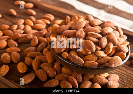 Full bowl of almonds on wooden background - Stock Photo