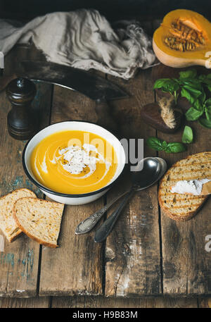 Pumpkin cream soup with fresh basil, spices and grilled bread - Stock Photo