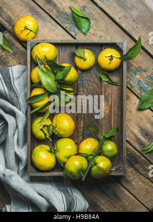Fresh green and orange tangerines with leaves in wooden box - Stock Photo