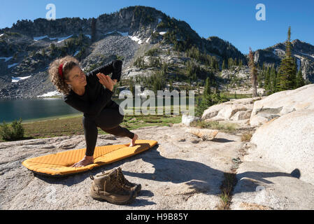 Backpacker doing yoga at a camp high in Oregon's Wallowa Mountains. - Stock Photo