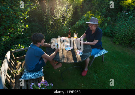 Grandmother playing cards with grandchild, Bavaria, Germany - Stock Photo
