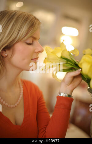 Young woman smelling a flower - Stock Photo