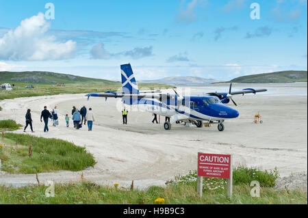 Airport and aircraft Twin Otter from Scottish airline Loganair, passengers when boarding, Airfield on sandy beach, - Stock Photo