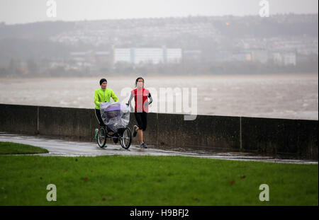 Swansea, UK. Monday 21 November 2016 Two women with a baby buggy jog by Mumbles promenade in Swansea, Wales, UK. - Stock Photo