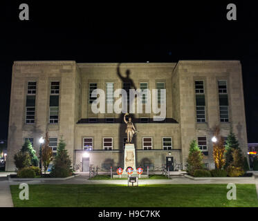 The Huron County Courthouse in Goderich Ontario, Canada illuminated at night casting a shadow of the a war memorial - Stock Photo