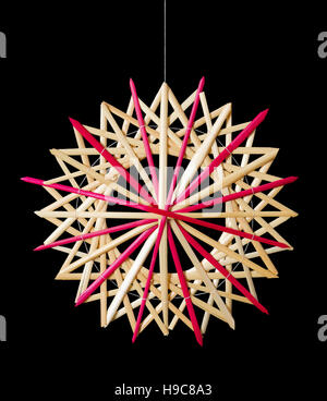Straw star Christmas decoration on black background. Handmade colorful decor for windows, as gifts or to hang on - Stock Photo