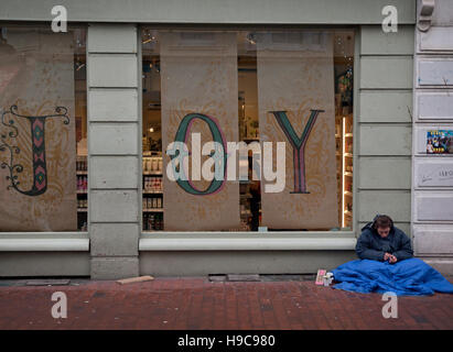 A homeless man sits on the pavement by a joyful shop window display in Brighton - Stock Photo