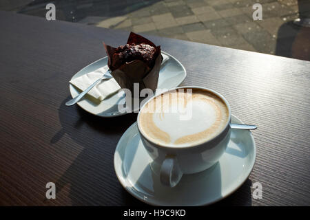 A cup of coffee with a heart drawn in the milk froth, and a chocolate muffin on a table, Dusseldorf, Germany - Stock Photo