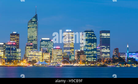 Dusk falls over the city of Perth, the capital of Western Australia. The Swan River can be seen in the foreground. - Stock Photo