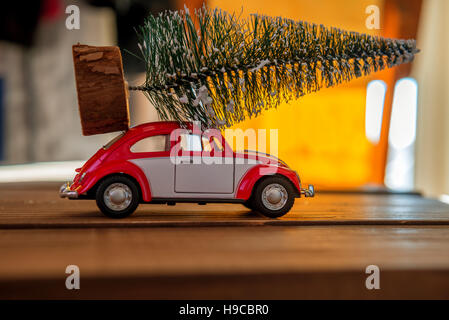 Red Car Carrying A Christmas Tree in sunset - Stock Photo