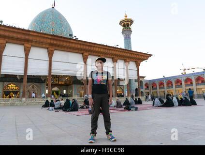Iranian boy in front of the mausoleum of shah-e-cheragh, Fars province, Shiraz, Iran - Stock Photo