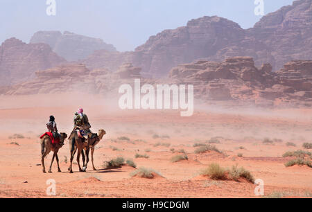 People on camels going through the desert storm - Stock Photo