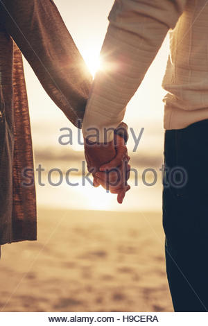 Close up rear view of a romantic senior couple holding hands against sea at sunset. - Stock Photo