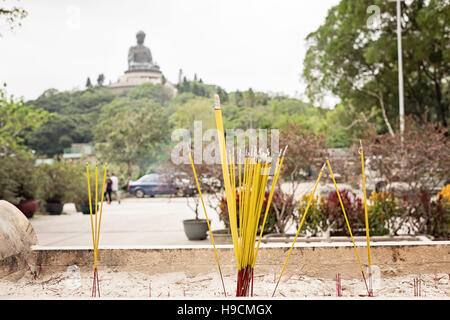 Incense sticks in the foreground with Big Buddha (Tian Tan) in the background - Stock Photo