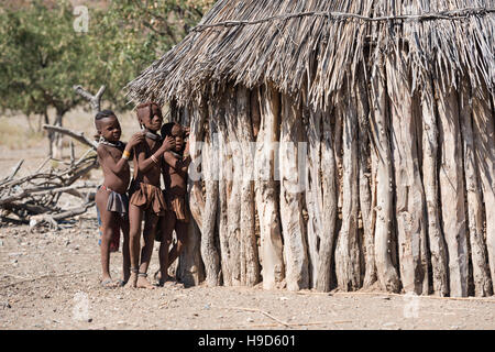 Children of indigenous Himba tribe in traditional clothes are playing with each other near their hut at Kunene Region - Stock Photo